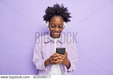 Happy Dark Skinned Woman Smiles Gladfully Reads Received Message Listens Music Via Wireless Headphon