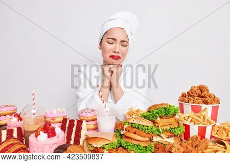Binge Eating Concept. Stressed Unhappy Asian Lady Wants To Eat Fast Food Tempting And Looks With App