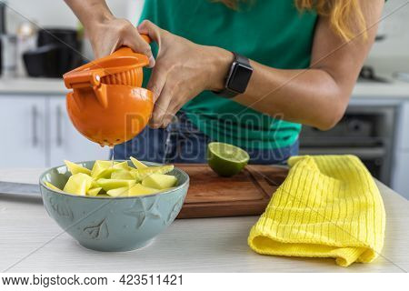 Woman Squeezing Lemon Over Mango In A Bowl In The Kitchen