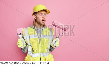 Startled Male Industrial Worker Makes Repairment In Apartment Holds Painting Roller And Brush Stares