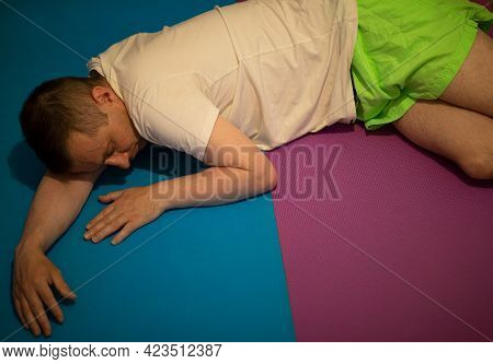 Man Is Lying Unconscious. First Aid And Recovery Position. The Mouth Is Downward So That Fluid Can D