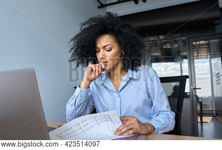 Concerned African American Businesswoman Ceo Analyst Sitting At Desk Reading Papers Financial Report