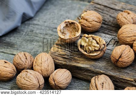 Ripe And Raw Whole Big Walnut Kernel With Shell On Rustic Backdrop. Healthy Nut Food For Brain