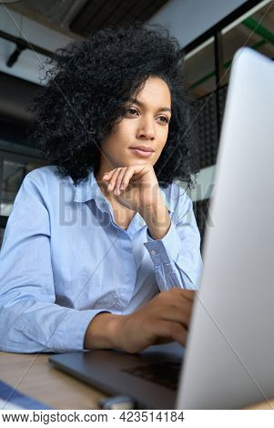 Young Serious Concerned African American Businesswoman Sitting At Desk Looking Laptop Computer In Co