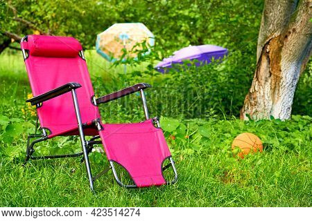 Red Chaise Lounge Chair On Summer Green Meadow