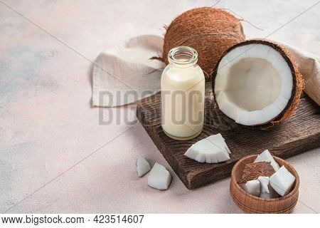 Vegetable Milk, A Healthy Drink Made From Coconut. A Bottle Of Coconut Milk And A Coconut On A Light