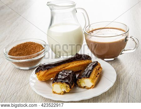 Bowl Of Cocoa Powder With Sugar, Pitcher With Hot Milk, Cup Of Cocoa With Milk, Whole Eclair With Ch