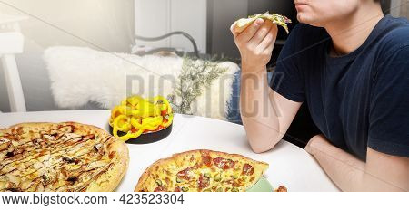 A Man Holds In  Hand A Piece Of Pizza  On A White Table, Served With Different Pizzas And Sliced Swe