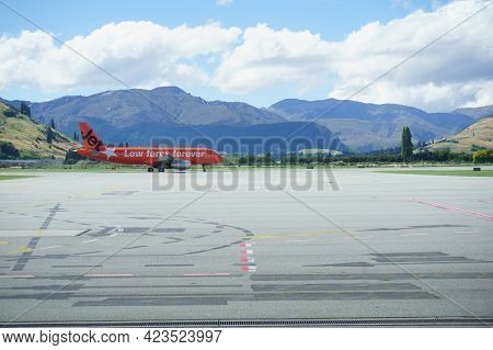 Queenstown, New Zealand - March 6 2015; Mountains Form Backdrop To Orange Color Plane Arriving At Ai