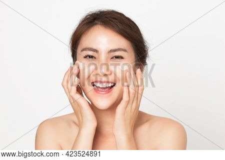 Asian Woman Looking Happy Applying Cream On Her Face. Young Female Applying Facial Skincare Cream.