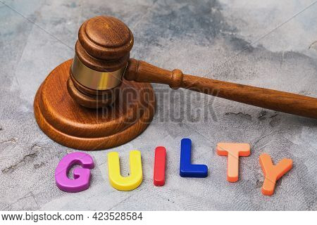 Judge Gavel And Word From Multicolored Plastic Letters On Table, Guilt Concept.