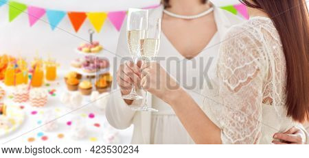 homosexuality, same-sex marriage and lgbt concept - close up of happy married lesbian couple hands holding and clinking champagne glasses over party background
