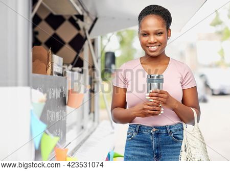 sustainability, eco living and people concept - smiling african american woman with thermo cup or tumbler for hot drinks and string bag over food truck background