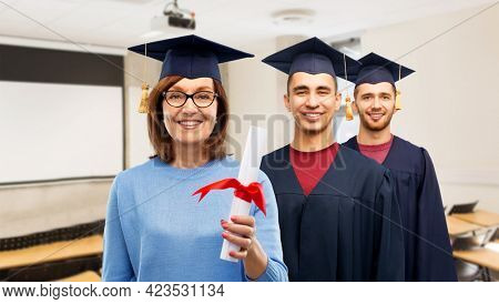 graduation, education and old people concept - happy senior and young graduate students in mortar boards with diploma over school classroom background