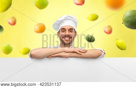 cooking, culinary and people concept - happy smiling male chef in toque with big white board over fruits on illuminating yellow background