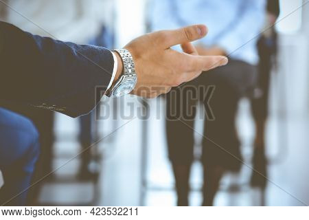 Business Man Making Presentation To Group Of People, Close-up. Speaker Delivering A Seminar To His C