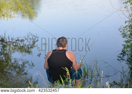 Male Fisherman Sits With  Fishing Rod On Bank Of River And Catches Fish. View From Back.
