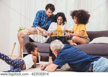 Lovely Home Family Stay Together In Living Room Father Mother And Grandfather Playing With Daughter