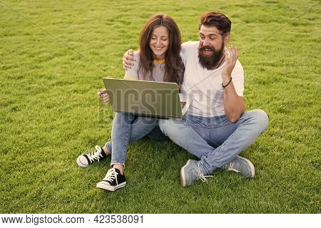 Technology In Leisure. Couple In Love Use Laptop On Green Grass. New Technology. Technology For Comm