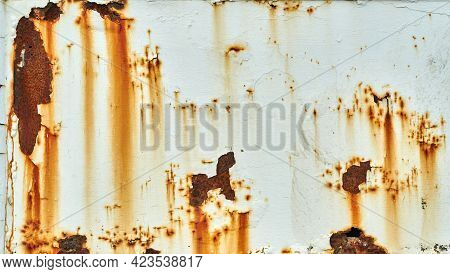 Rust With Cracked And Peeling Paint On A White Wall. Patches Of Rust Stain A White Painted Metal Sur