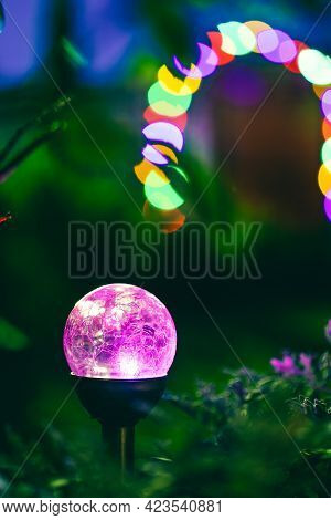 Night View Of Flowerbed Illuminated By Energy-saving Solar Powered Colorful Multi-colored Lantern On