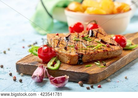 Grilled Tofu Steaks Are Served With Cherry Tomatoes, Green Onions And Peppers On A Wooden Serving Bo