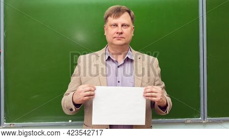 Strict Teacher With A White Sheet Of Paper At The Green Board Copy Space.