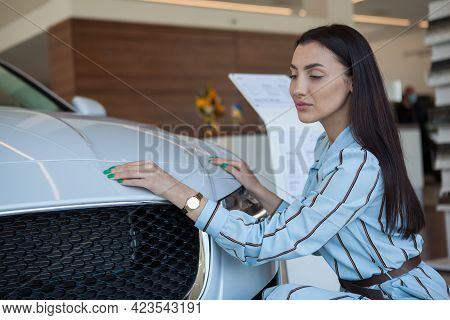 Attractive Woman Examining Luxury Car For Sale At Car Dealership