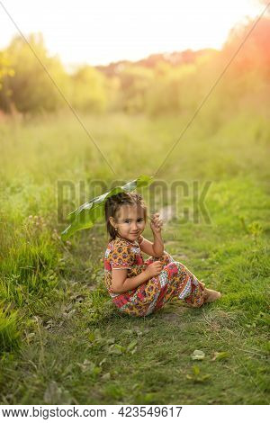 The Girl Is Hiding Under A Huge Burdock. The Girl Holds A Large Burdock Leaf, Like An Umbrella, To H
