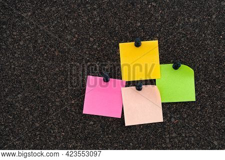 Colorful Note Papers On A Brown Cork Bulletin Board. Close Up.