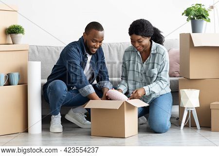 Happy African American Spouses Unpacking Cardboard Boxes With Belongings At New Flat