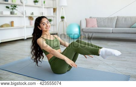Positive Athletic Indian Woman Doing Abs Exercises During Her Domestic Workout, Indoors