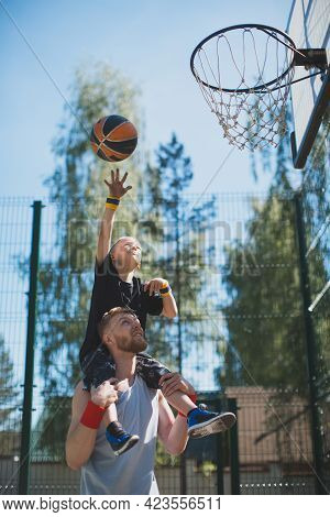 Dad And Son Playing Basketball Outdoors. Basketball Player Kid Boy On Fathers Shoulders Throw Ball T