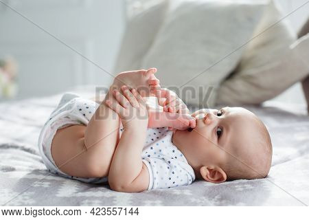 A Charming Boy In A White Sunny Bedroom Plays Alone, Lying On The Bed. A Charming Cute Little Boy Wi