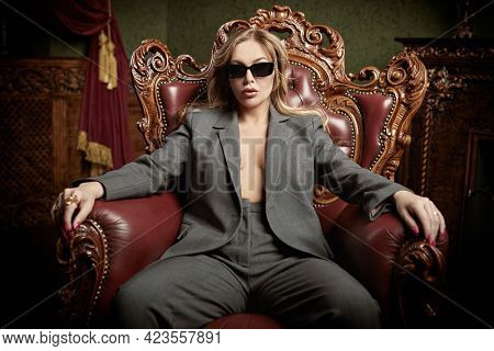 Sexual woman in fashionable pantsuit and black sunglasses alluring in a vintage armchair in a luxury apartments. Wealthy lifestyle. Fashion shot.