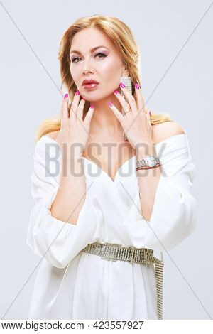 Portrait of a stylish sexy middle aged woman with enlarged full lips and evening makeup posing in precious jewelry. Beauty, fashion. White background.