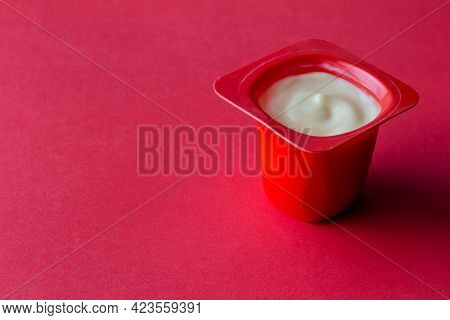 Yogurt Cup On Red Background - Delicious Fruit Yoghurt In Red Plastic Pot With Copy Space