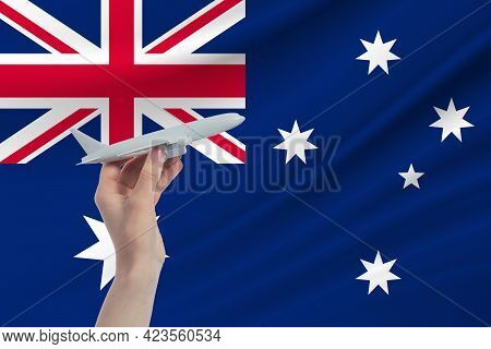 Airplane In Hand With National Flag Of Australia. Travel To Australia.