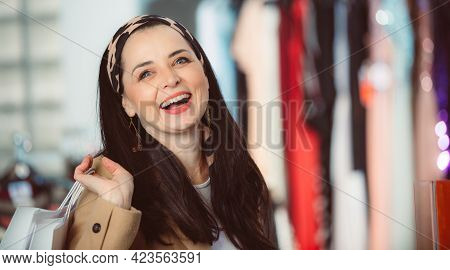 Pretty Young Woman With Full Bags Of Clothes Enjoying Shopping Clothes In A Shopping Center, Smillin