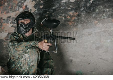 Young Man In A Paintball Action With Professional Equipment, Mask, Gun And Protective Helmet, Simula