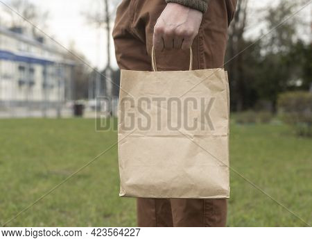 Hand With Brown Craft Pack Or Packet In Hand On City And Grass Background.