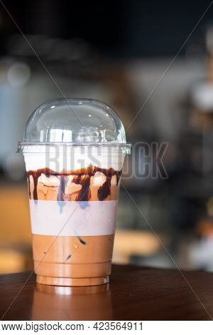 Iced Mocha Coffee In Plastic Take Away Cup On Wood Table In Coffee Shop