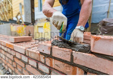 Bricklayer Is Laying Brickwork On Exterior Wall With Putty Knife In Construction Site.