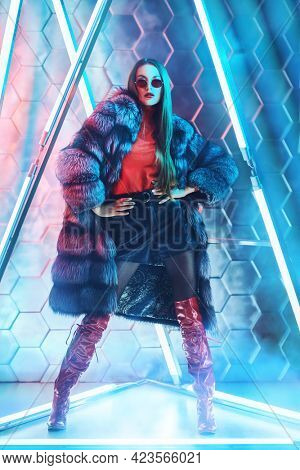 Full length portrait of a stunning fashion model girl in expensive silver fox fur coat posing among the neon lamps. Modern fur coat fashion.