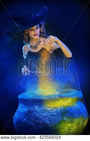 Halloween magic. A beautiful young witch in a hat and with a magic wand conjures over a cauldron.