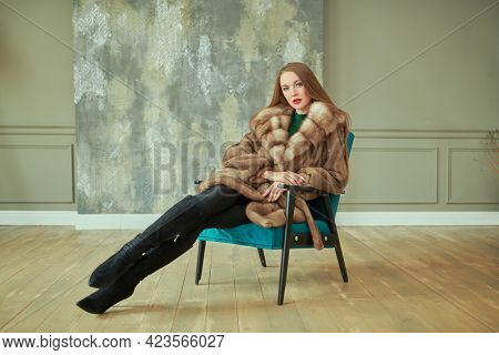 Full length portrait of a stunning glamorous woman in an expensive mink and sable fur coat posing in luxury apartments. Fur coat fashion.