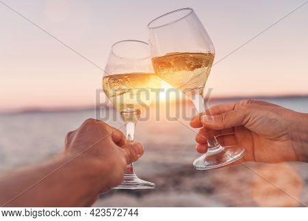 Couple In Love Clinking With White Wine Glasses While They Enjoying The Beautiful Pink Seaside Sunse
