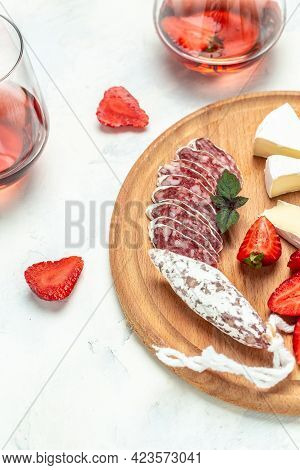 Antipasto Sliced Spanish Fuet Salami Wurst, Camembert Cheese, Strawberries And Glass Rose Wine On Wh