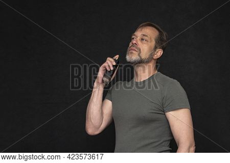 Portrait Of An Elderly Athletic Man With A Gray Beard And Wearing A Green T-shirt With Perfume On A