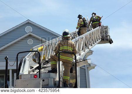 Three Firefighters Climbing A Ladder Fireman At Work Extinguishing Fire
